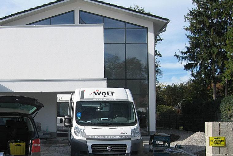 Auto von Holzbau Wolf vor dem Holzhaus